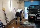 Motocyklista na myjni - pranie kombinezonu myjką ciśnieniową