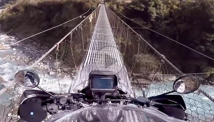 Motocyklem przez rzekę w Himalajach - most linowy w Annapurna w Nepalu