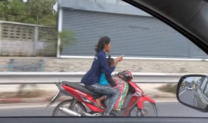 kobieta na skuterze z dzieckiem i smartfon