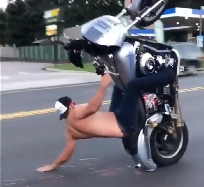 motocyklista bez koszulki jazda na gumie miedzy samochodami stunt w ruchu ulicznym