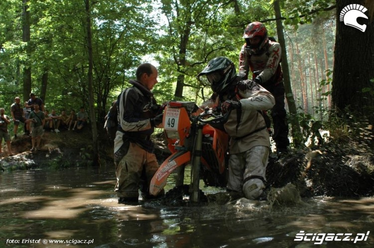 zawodnicy przeprowadzaja motocykl